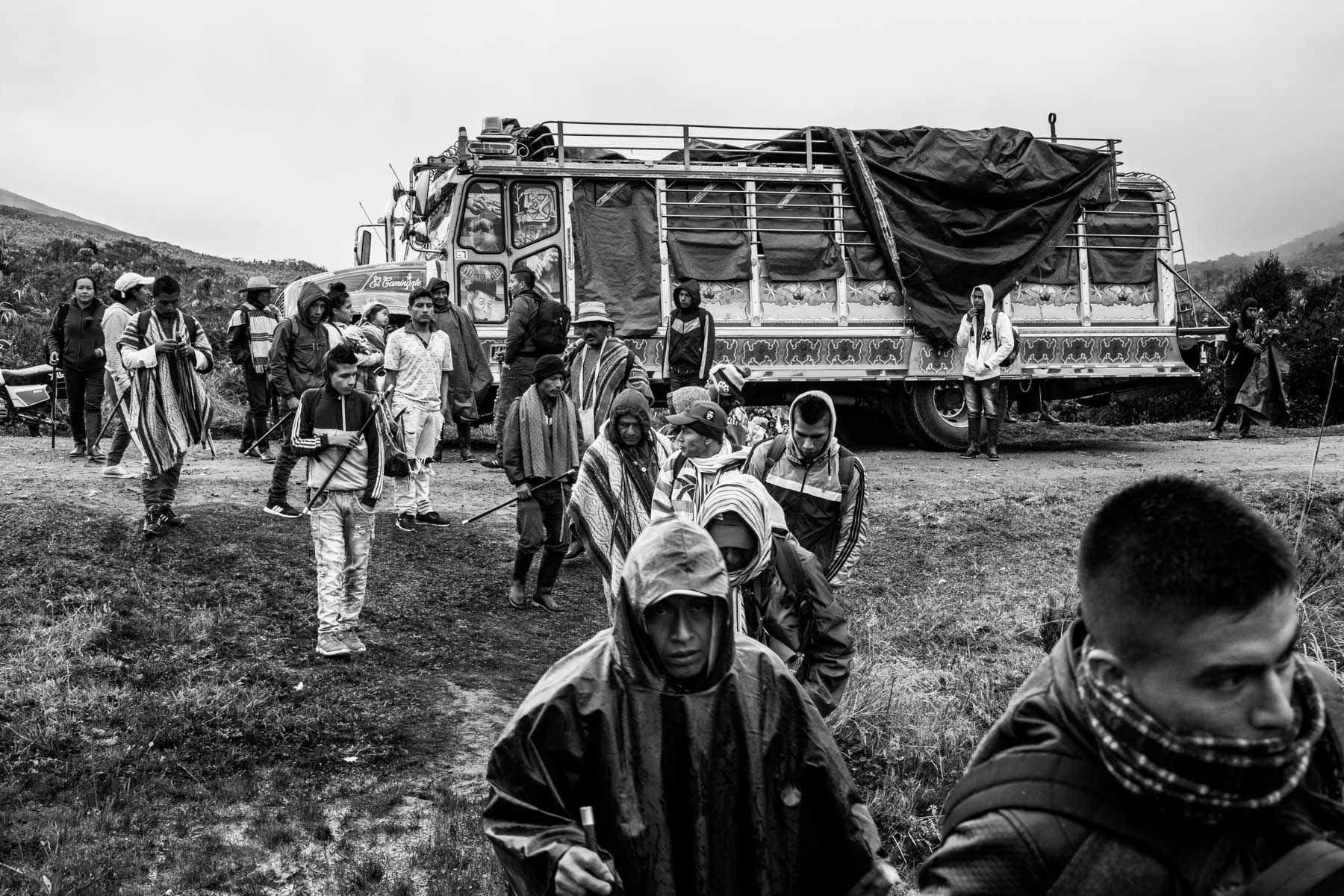 """Members of the Nasa indigenous  community of Tacueyó get out of the 'chiva' (bus) in the Páramo of Pisnos to start the celebration of the 'Khabu fxizehnxi' ('Refreshing of the Batons""""), one of the five main rituals of the Nasa indigenous people of the Cauca region in Colombia.  Cauca region, Colombia, January 2019."""