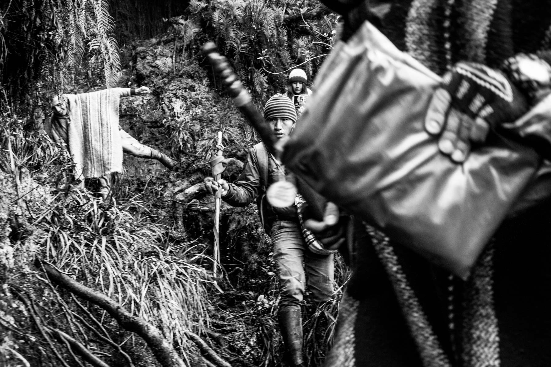"""People from the Nasa indigenous community climb a sacred mountain in the Páramo de Pisnos to make an offer as part of the cleansing ritual of the 'Khabu fxizehnxi' ('Refreshing of the Batons""""), one of the five main rituals of the Nasa indigenous people of the Cauca region in Colombia. Cauca region, Colombia, January 2019."""