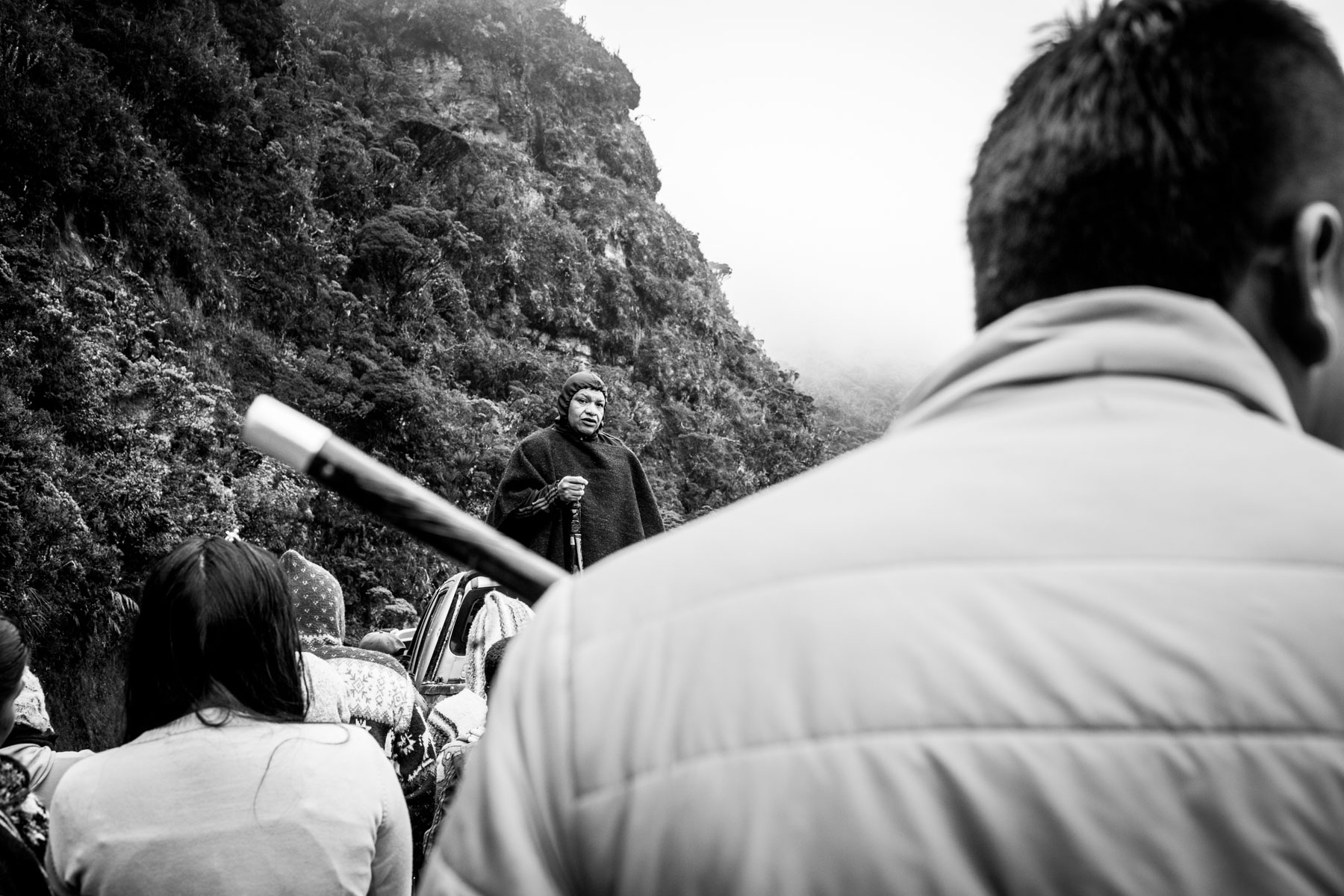 """Political leader from the Nasa indigenous reservation of Tacueyó speaks to the community in the Páramo de Pisnos after the celebration of the cleansing ritual of the 'Khabu fxizehnxi' ('Refreshing of the Batons""""), one of the five main rituals of the Nasa indigenous people of the Cauca region in Colombia. The leader warns the community about the  threats and murders that are increasing exponentially within the territory. Cauca region, Colombia, January 2019."""