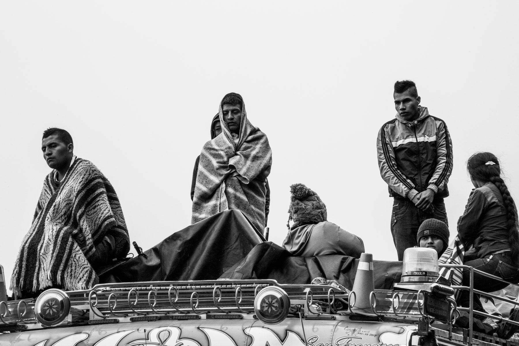 "Members of the Nasa indigenous community stand on the roof of a 'chiva' (bus) while listen to the speech of their political leader at the end of the celebration of the cleansing ritual of the 'Khabu fxizehnxi' ('Refreshing of the Batons""), one of the five main rituals of the Nasa indigenous people of the Cauca region in Colombia. The leader warns them about the  threats and murders that are increasing exponentially within the territory. Cauca region, Colombia, January 2019."